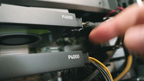 LONDON, UNITED KINGDOM - CIRCA 2017: Male hand verifying the power connector of two NVidia Video card model P4000 connected in sli on powerful workstation