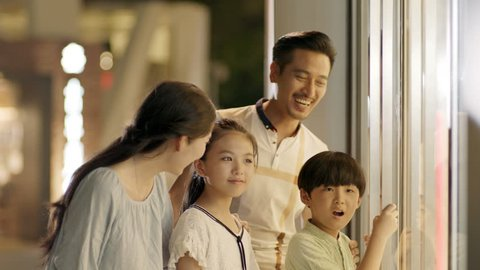asian family of 4 standing & looking into shop window in slow motion