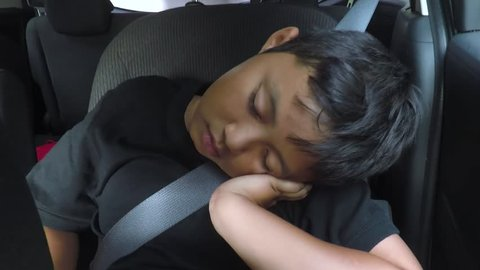 Video footage of a cute tired little boy sleeping inside a car while leaning on his hand, shot at a road trip
