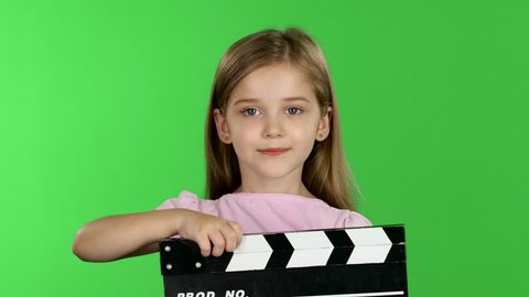 Baby holds in hands clapperboard. Green screen