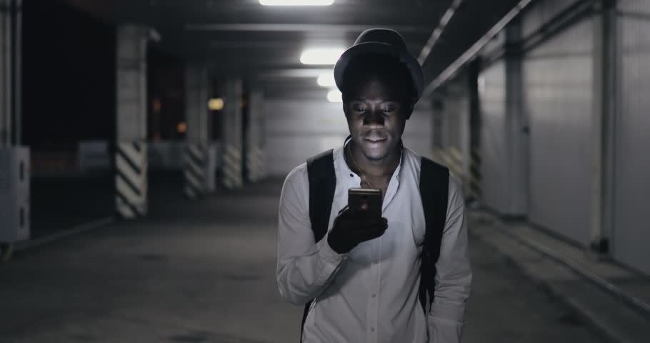 African man in hat using smartphone stroll in the parking at night | Shutterstock HD Video #30195787