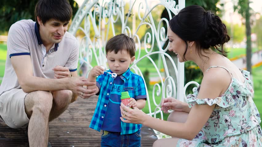 Father mother and son are peacefully playing in the park, blowing bubbles and catching them at the day time. | Shutterstock HD Video #30197047