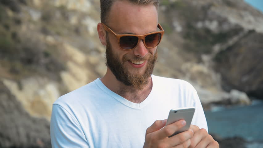 Young man is sitting on a stone and using smartphone near the sea. Portrait of handsome guy with mobile phone at the ocean beach. Boy looking at phone app. He texting sms or chatting in social network | Shutterstock HD Video #30228997