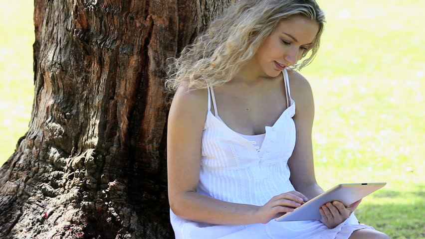 Pretty girl in floral dress reading absrobing book under the tree video of a woman sitting in a park using an ebook hd stock footage clip fandeluxe Ebook collections