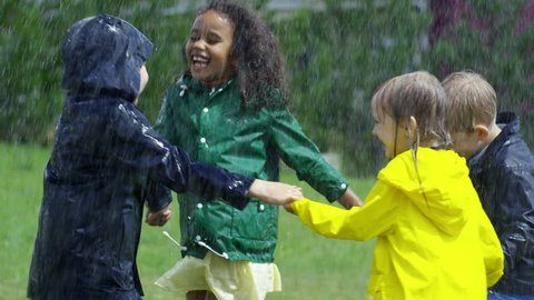 Slow motion with tilt down of happy little boys and girls in rubber boots and raincoats holding hands and running and jumping up in circle on green grass during heavy rain