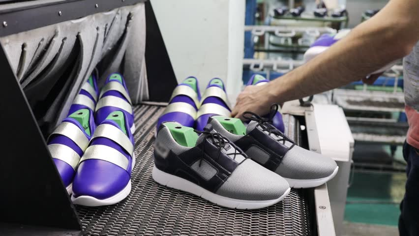 Conveyor with sneakers pairs in workshop and male hands in shoes factory, slow motion