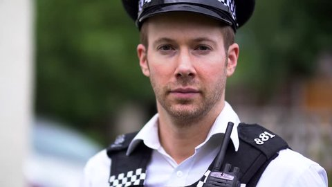 Portrait Of A Police Officer, Serious and Brave, Close Up in Slow Motion. Wearing Black and White Uniform Including Hat. White Caucasian in 30's.