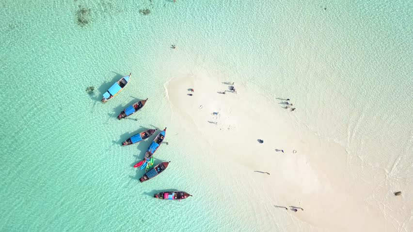 4K Aerial or top view of long tail boats at the white sand bar beach with crystal clear water.Summer beach in Phuket Thailand