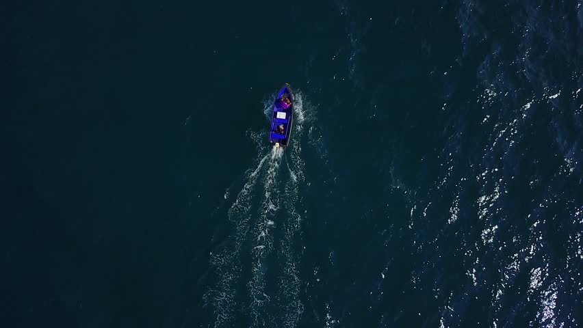 Small motor-driven fishing skiff sail at deep blue sea waters, top-down aerial perspective. Camera follow little boat, fly over water surface