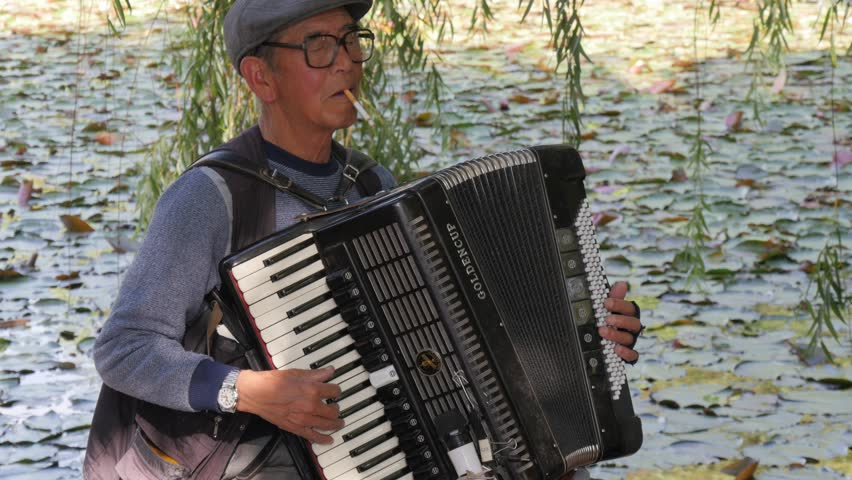 Kunming,China - May 20,2017: Man playing accordion in park