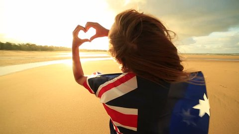 Female on beach makes heart shape finger frame, Australian flag Young woman on the beach at sunset makes a heart shape finger frame towards the sunset, she is wrapped in an Australian flag.