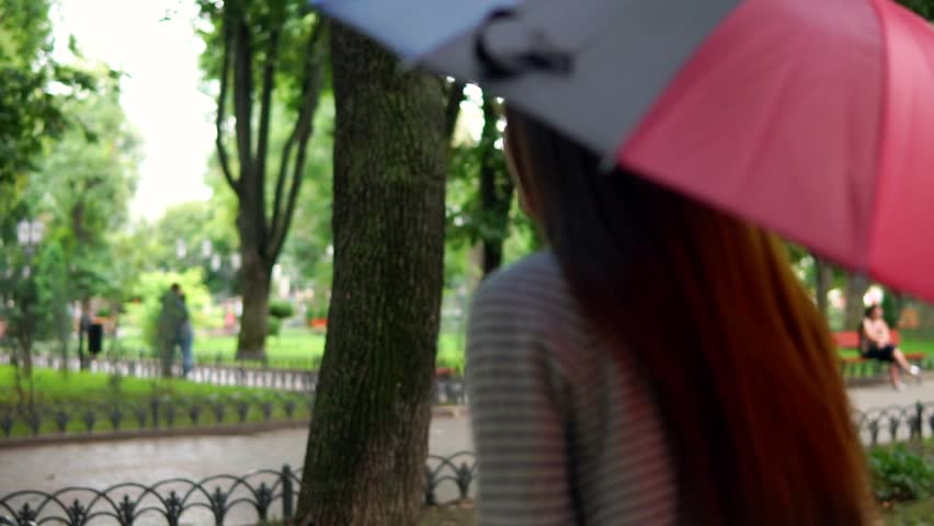 Back view of an unrecognizable woman running with colorful umbrella under the rain in the city park. Slowmotion shot