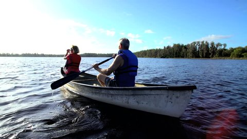 Healthy Caucasian American seniors wearing lifejackets enjoying their outdoor leisure kayaking on the lake