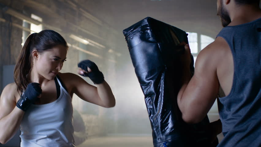 Athletic Woman Trains Her Punches on a Punching Bag that Her Partner/ Trainer Holds. She's Strong and Gorgeous Woman. They Workout in a Gym. Shot on RED EPIC-W 8K Helium Cinema Camera.