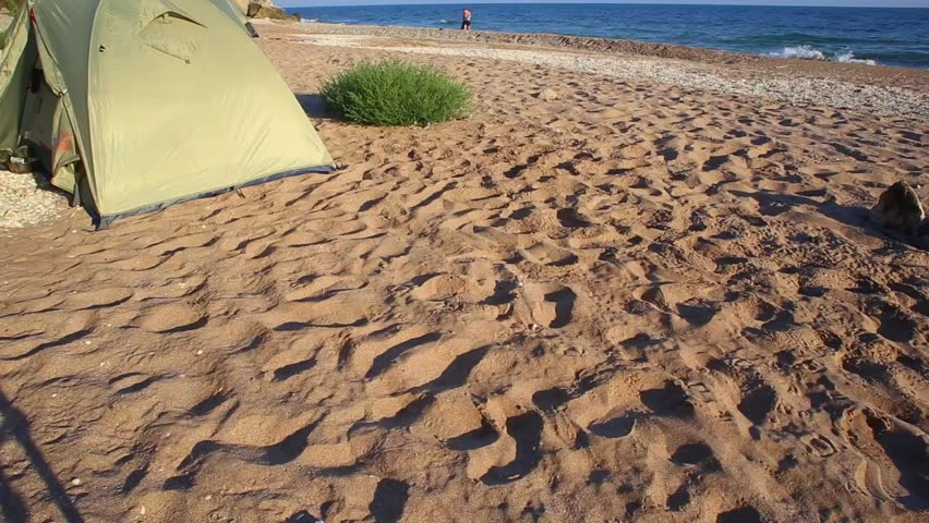 Tent stands under wind on Wild seashore with sandy beach, surf waves under morning sunlight and human figure far away.  Tracking up. | Shutterstock HD Video #30314647