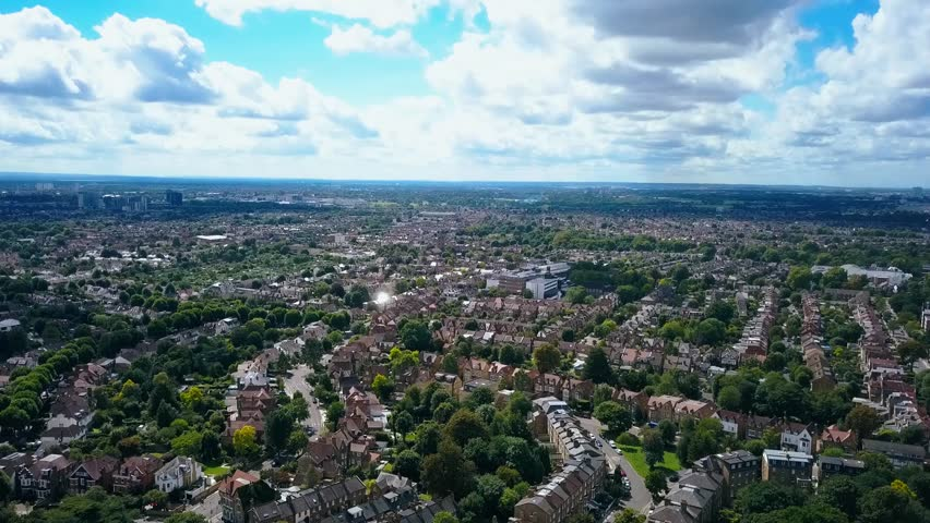 Aerial view of a leafy UK suburb on a summers day - camera lowers