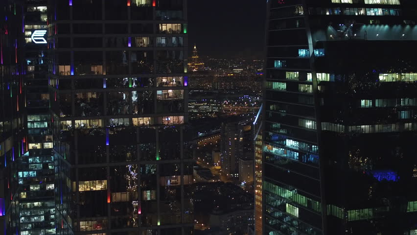 Unique Aerial flight around and approach to windows of Moscow City business center. Evening illumination. Offices from outside. Managers employees work. Quadcopter drone beautiful 4K shot