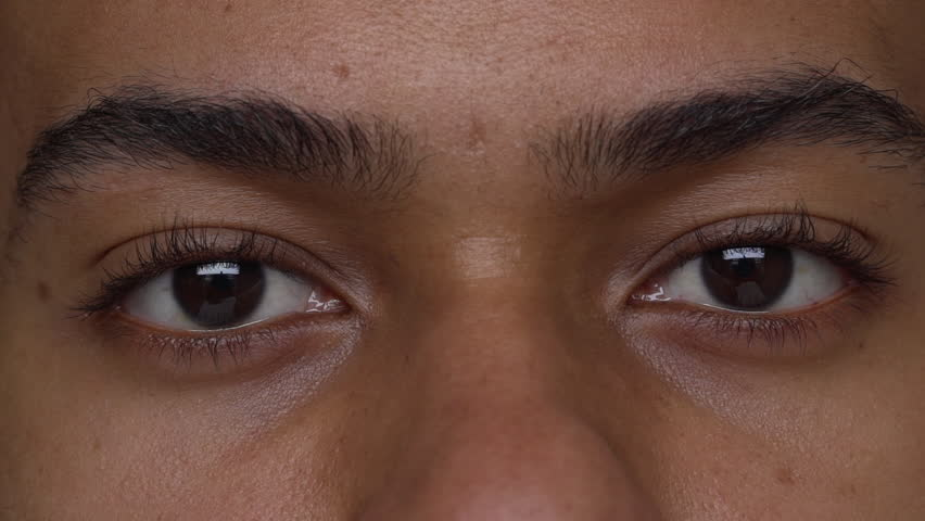 extreme close up beautiful eyes of tan man expressing anger slow motion. Facial expressions, concept of emotions