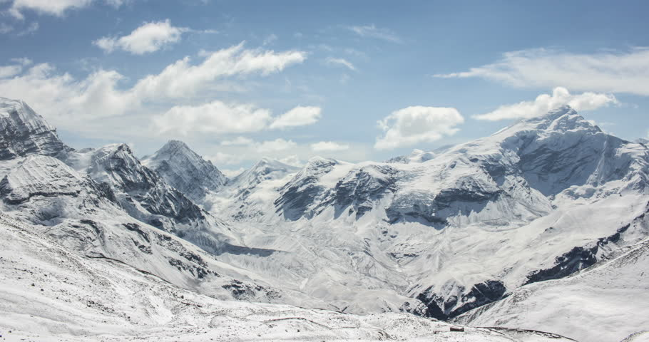 Time lapse of clouds running on blue sky over amazing white landscape of high rocky mountains and snowy valley