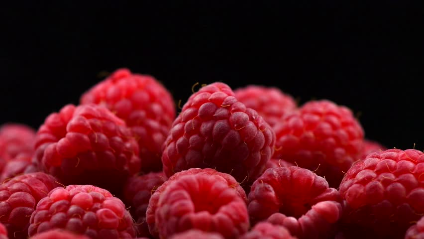 Raspberry rotation over black Background. Ripe fresh and juicy raspberries rotated close-up, isolated on black. Organic berry, healthy food. Diet, dieting 4K UHD video 3840X2160
