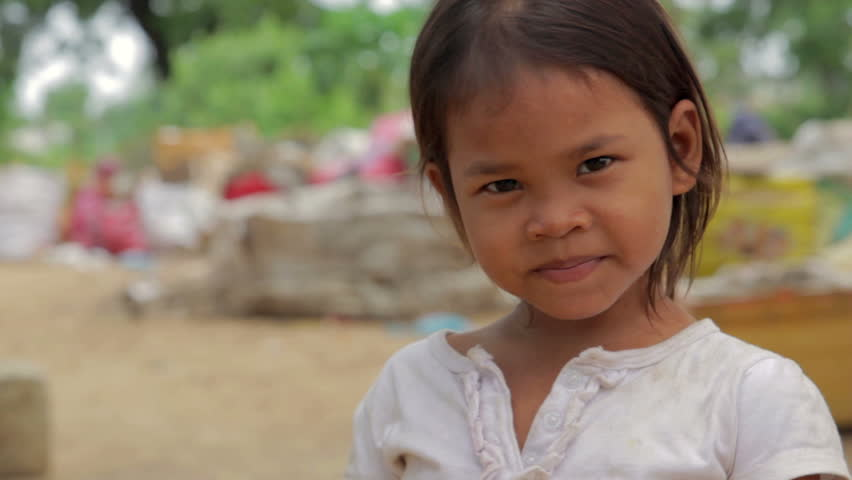 Cambodian girl in slums, garbage at background