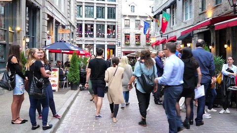 Montreal, Canada - May 27, 2017: Old town area with many crowd of people walking on street in evening by restaurants in Quebec region city