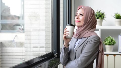 attractive beauty lady muslim business worker holding coffee mug standing in office and looking at window outside daydreaming relaxing.
