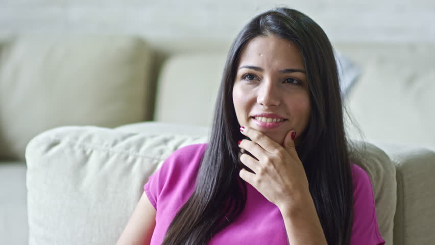 PAN of smiling Hispanic woman sitting in armchair and listening unrecognizable man talking
