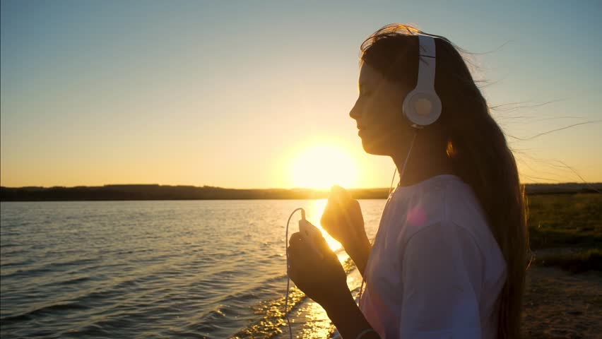 Teenage girl in headphones dancing at sunset evening listening to music on phone. Slow motion. #30449977