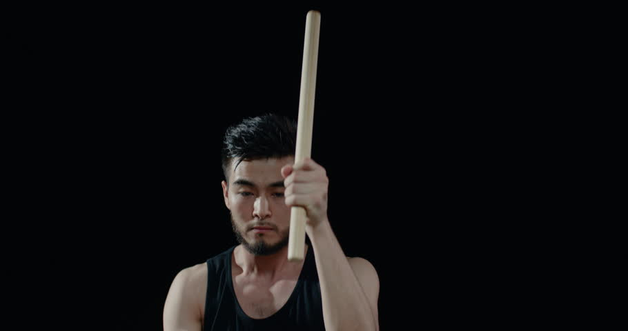 performance of Taiko , close-up Asian male drummer in black clothes, beats a rhythm on a Japanese drum,black background