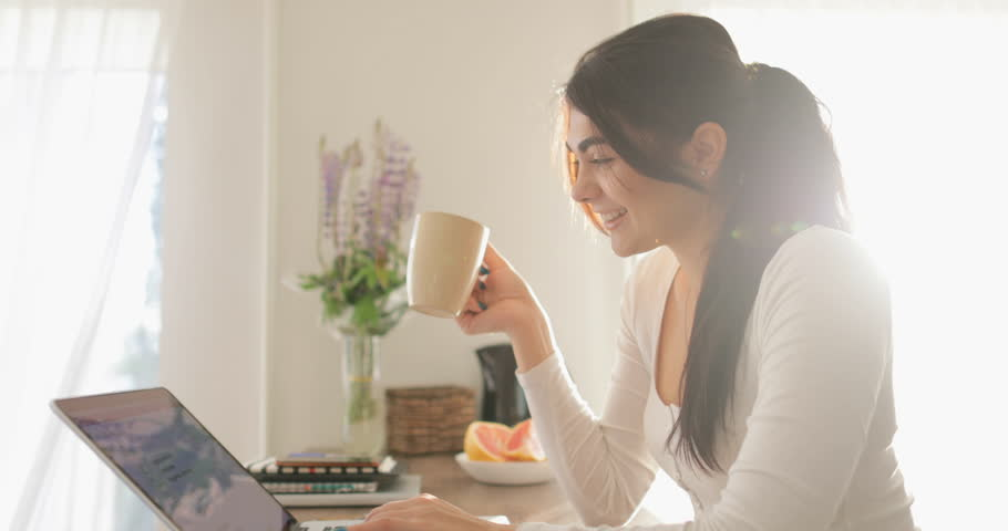 home office multitasking. unique office young woman work on laptop computer drinking coffee morning sitting at  table home beautiful girl intended office multitasking