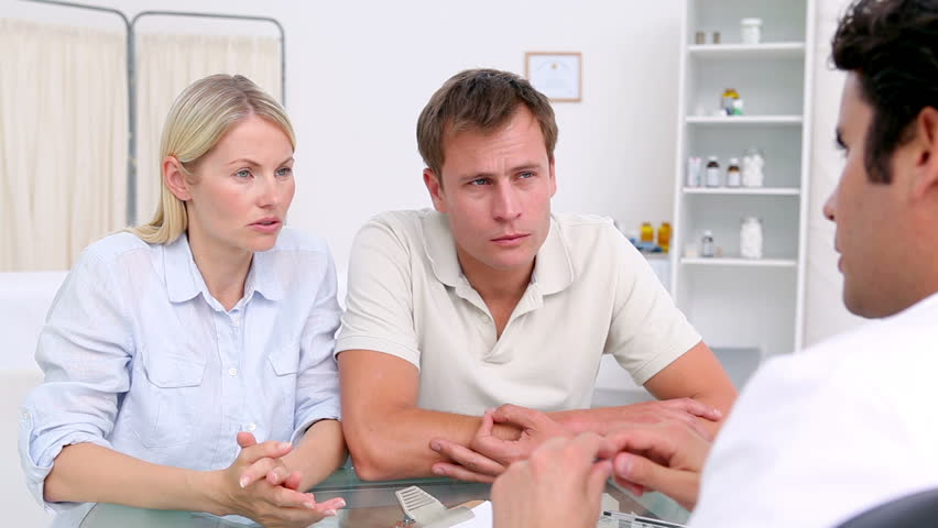 Disappointed couple sitting in front of their doctor in his office