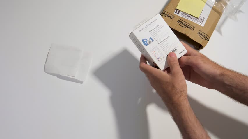 PARIS, FRANCE - CIRCA 2017; man point of view of unboxing process of new parcel from Amazon prime containing smartwatch activity and sleep tracker made by Nokia Health (Withings) | Shutterstock HD Video #30488167