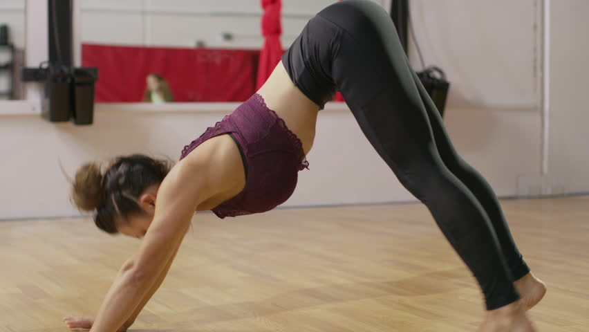 Medium shot of woman stretching back and leg in gymnasium / Midvale, Utah, United States