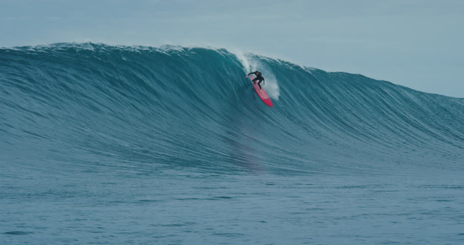 Surfer rides giant blue ocean wave. Shot on RED in 4k. Big wave surfing. Slow motion