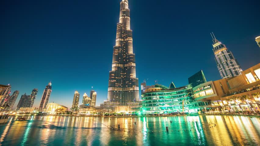 DUBAI, UAE - MAY 2017: Timelapse dancing fountain near Burj Khalifa illuminated by the city at night. Burj Khalifa is the tallest man-made structure in the world