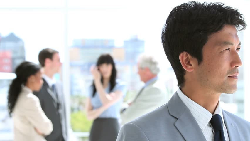 Happy businessman standing upright in front of his team in a bright room | Shutterstock HD Video #3051133
