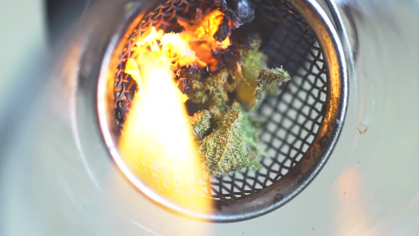Macro burning of cannabis in super slow motion, the process of smoking a bong medical marijuana. Smoke weed