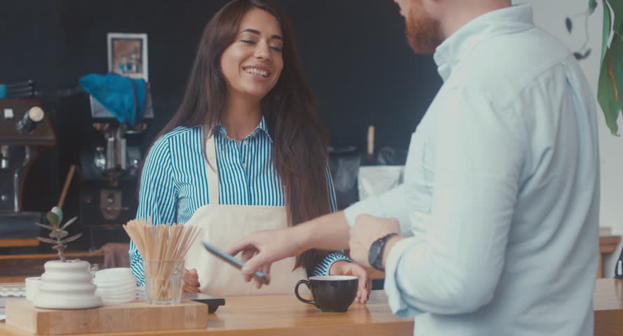 Attractive Caucasian female employee serving a coffee and taking mobile phone NFC payment from customer at modern coffee shop. 4K UHD 60 FPS #30553432