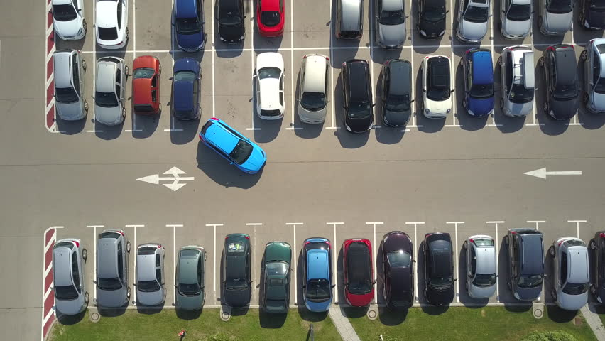 AERIAL TOP DOWN, TIMELAPSE: Bad driver incapable to park a car on parking space in big crowded parking lot. Driver having problems, unable to park a car in parking spot. Parking fail on parkspace