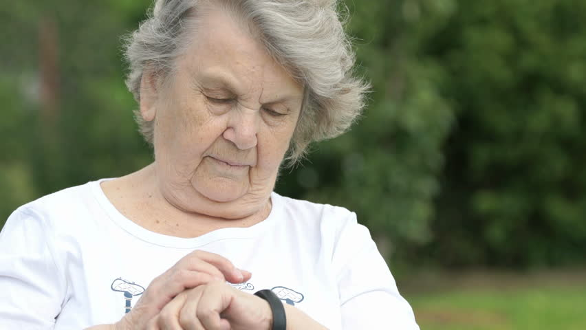 Mature old woman dressed in white t-shirt looks at the results of physical activity using a wristband fitness tracker then smiles and shows thumbs up sign in the background of the green park.