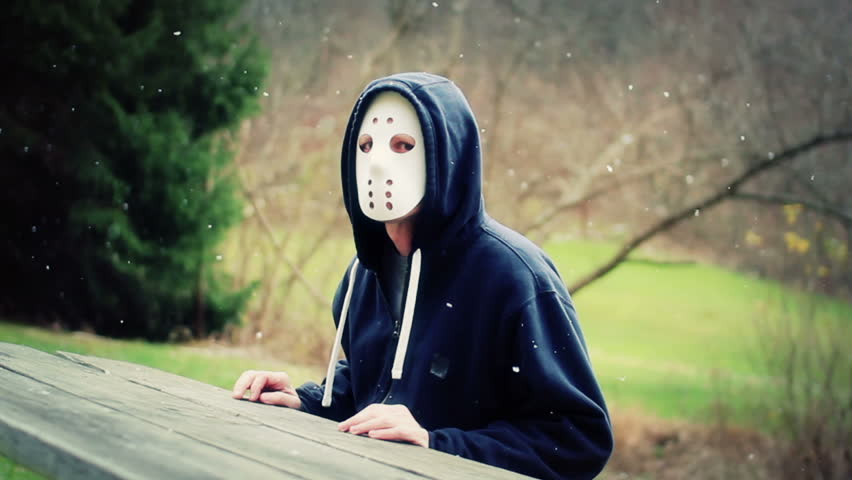 A masked killer sits at a picnic table waiting for a victim.