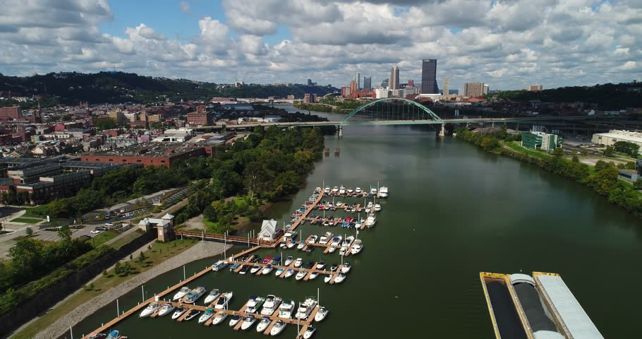A high angle right moving aerial establishing shot of a marina on the Monongahela River with the Pittsburgh skyline in the distance.     Shutterstock HD Video #30604021