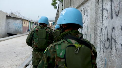 Close up following UN peacekeepers walking closesly to a wall down an empty street