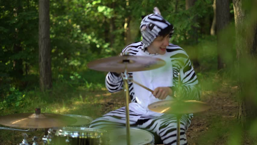Man in zebra costume plays on drums, smiles, enjoys, go crazy in forest between trees. Drummer is playing music on the grass