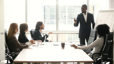African businessman presenting business offer to partners, black man giving presentation to clients at meeting in conference room, dark skinned team leader reporting about work result with whiteboard