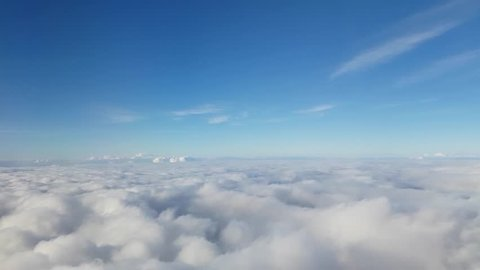 Stunning footage of aerial view above clouds from airplane window with blue sky. Shot in 4k resolution