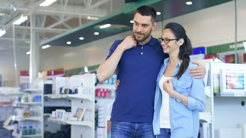 In the Electronics Store Beautiful Young Couple Looks at Latest Tablet Computer,They Think about Buying One.Store is Big, Bright and Has all the New Devices.Shot on RED EPIC-W 8K Helium Cinema Camera. | Shutterstock HD Video #30614407