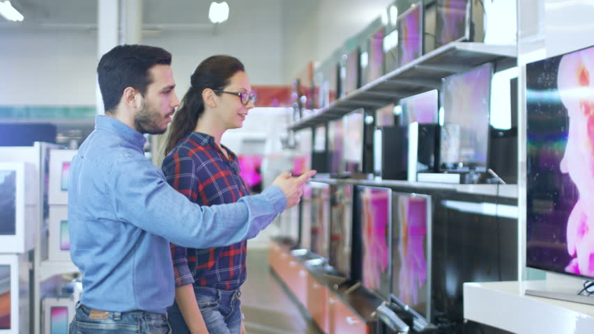 Young Couple Shopping for a New 4K UHD Television Set in the Electronics Store. They're Deciding on the Best Model for Their Happy Family House. Shot on RED EPIC-W 8K Helium Cinema Camera.