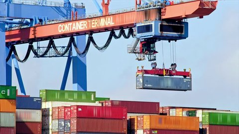 Gantry crane is unloading a container from a ship at daytime in the port of Hamburg / Germany.